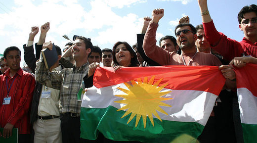 Young Kurdish Iraqis carry the flag of the Kurdistan Regional Government in Iraq