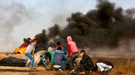 Manifestantes palestinos se ponen a cubierto durante enfrentamiento con las tropas israelíes junto a la frontera entre Gaza e Israel, al este de Khan Younis, en la Franja de Gaza, el 5 de abril de 2018.