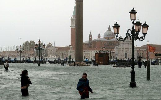 La gente camina en la inundada Plaza de San Marcos durante un período de marea estacional en Venecia, Italia, 29 de octubre de 2018.