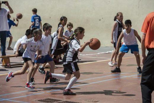 Niños y niñas juegan juntos al baloncesto.