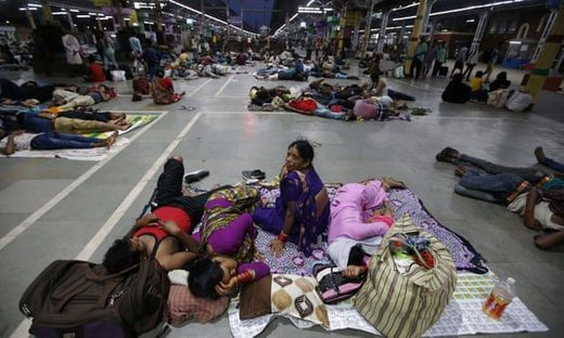 Stranded passengers rest inside a railway station after trains between Kolkata and Odisha were cancelled due to Cyclone Fani