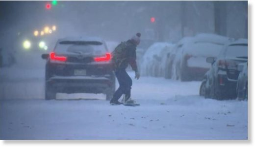 A person tries to ride a snowboard down the road in Denver Wednesday morning.