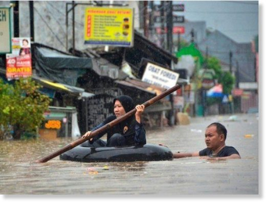 A woman paddles through flood waters on an inner tube in Bekasi, near Jakarta.