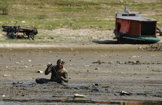 A fisherman searches for eels in the mud of the dried up Paraguay River