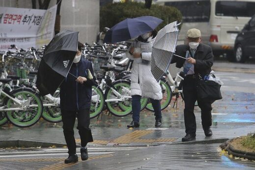 People wearing face masks try to manage their umbrellas in the rain in Seoul