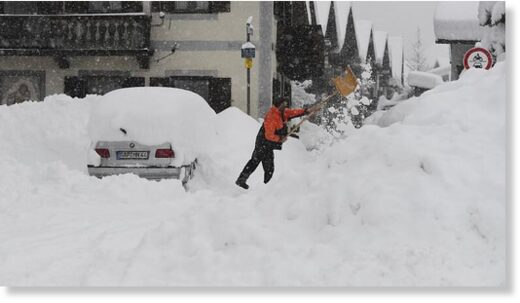 A man shovels his car free of snow after days of snowfall in Garmisch-Partenkirchen, southern Germany, Monday, Jan. 18, 2021.   -