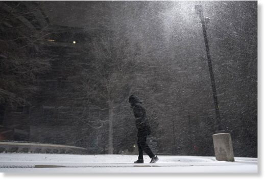 A woman walks through falling snow in San Antonio, Texas on Sunday.