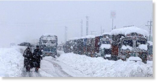 People walk past stranded vehicles on the Jammu-Srinagar National Highway during heavy snowfall, at Qazigund in Anantnag district of South Kashmir.
